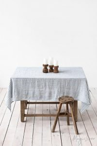 Linen tablecloth with a wooden stool and candles