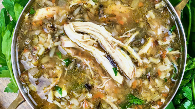 Chicken and wild rice soup in a pan surrounded by fresh herbs
