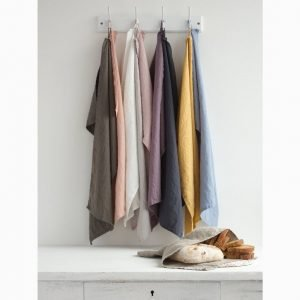 Linen tea towels that pop with colour hanging on a rack
