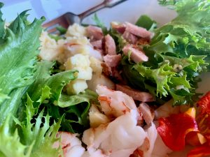 A Cobb salad of shrimp, peameal bacon, leafy lettuce, nasturtium flowers