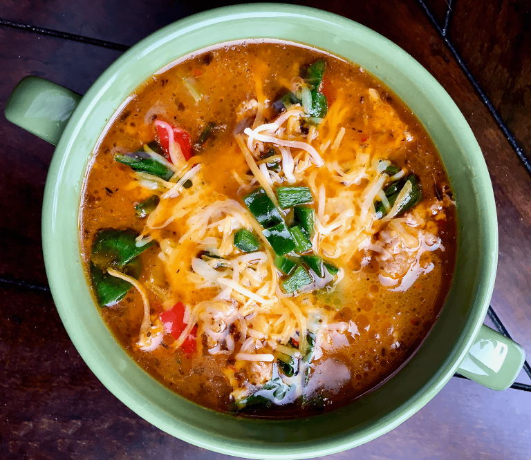 Spicy sausage soup with herbs, peppers, and spinach, garnished with melted cheese is delicious- birds-eye view