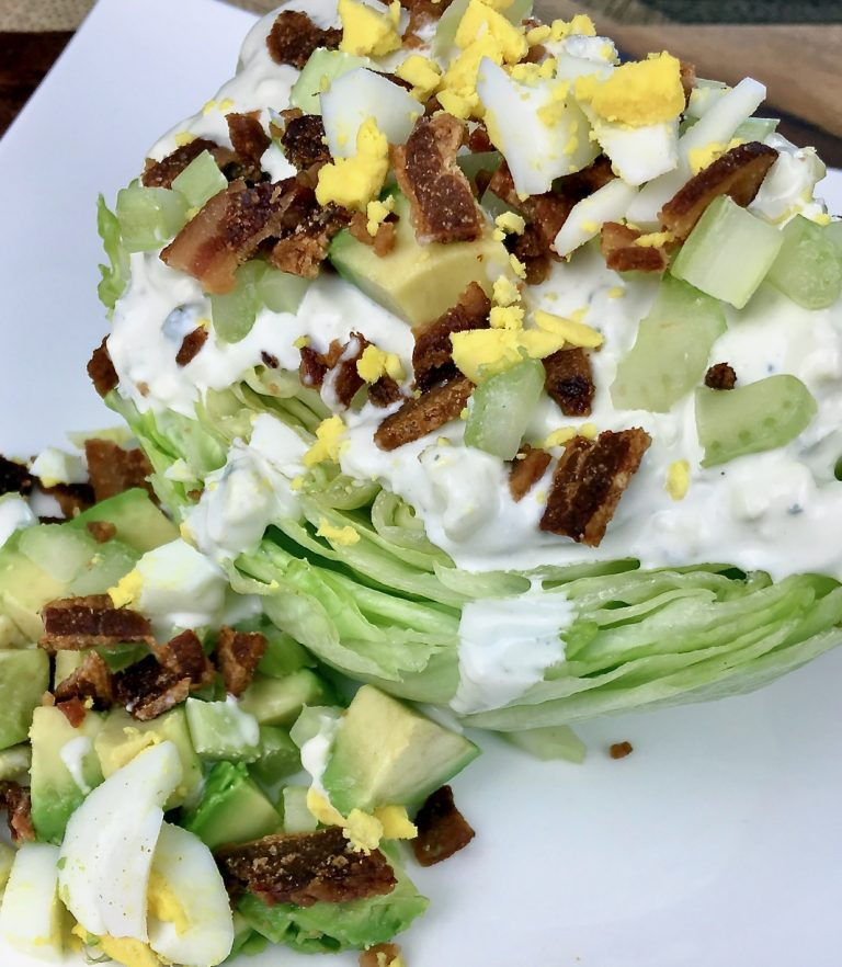 Wedge salad smothered in homemade blue cheese dressing and garnished with egg, crispy bacon, and celery