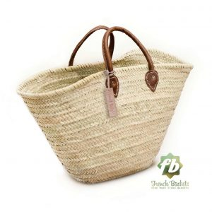 A handmade straw shopping basket with leather handles