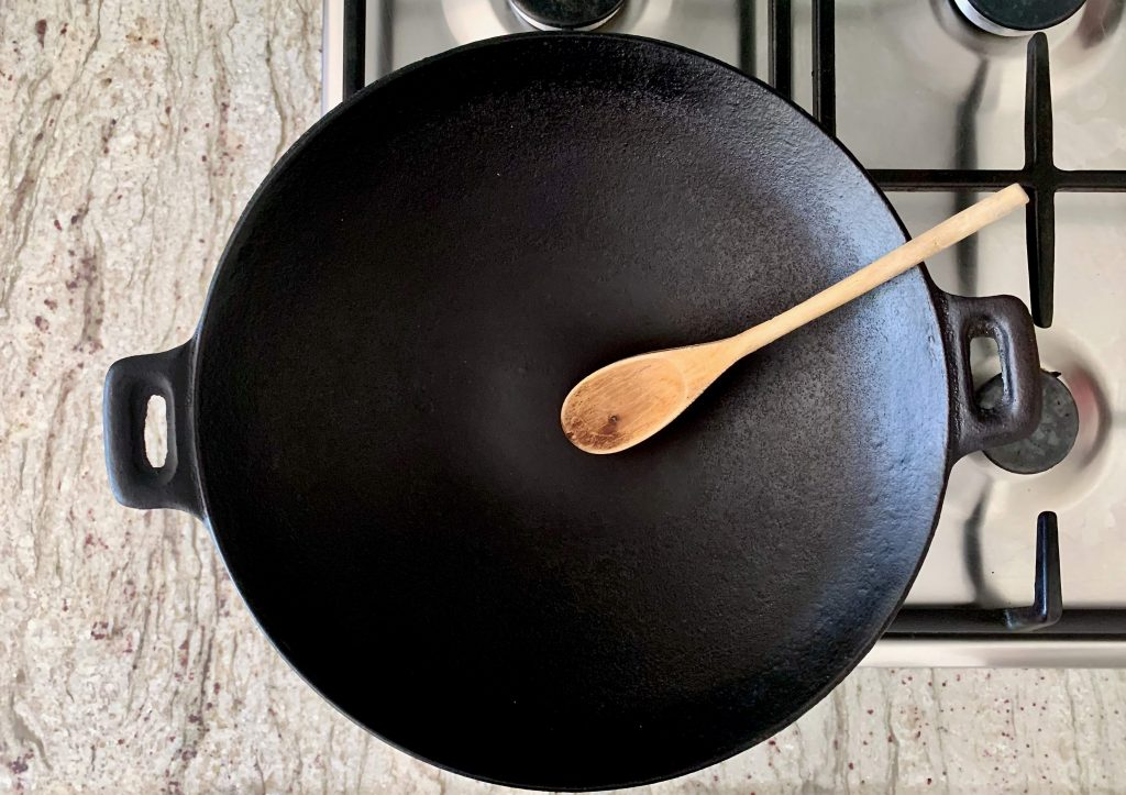 Cast iron wok on a gas stove top is often used for deep frying food and can be replaced by a air fryer
