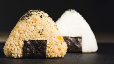 Two types of cooked rice piles, one is seasoned, the other is plain and both sit on a strip of dried seaweed