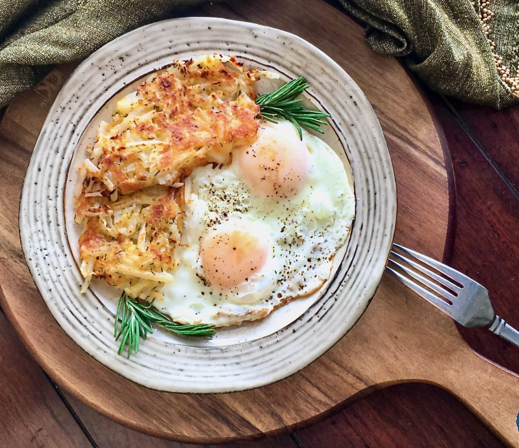 Hash browns served with two eggs on a wood platter for breakfast or a satisfying snack