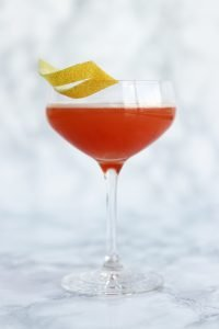 Paloma cocktail served in a wine glass garnished with a slice of lemon rind