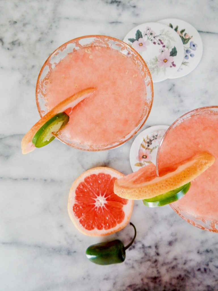 Paloma cocktail with a spicy slice of jalapeno