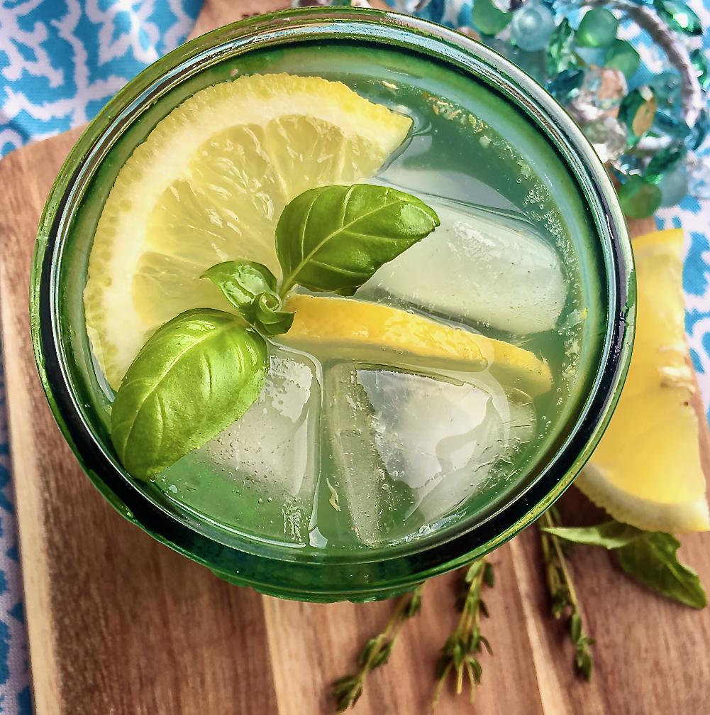 A Lemon Spritzer garnished with fresh basil leaves and lemon slices